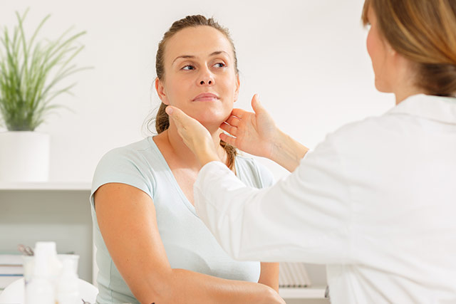 Doctor looking at female patients face